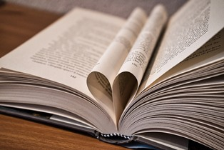 A photograph of an open book with pages folded inward to create a heart shape.